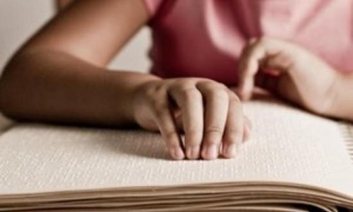 Pessoa de t-shirt cor-de-rosa a ler Braille. Créditos: Visualhunt