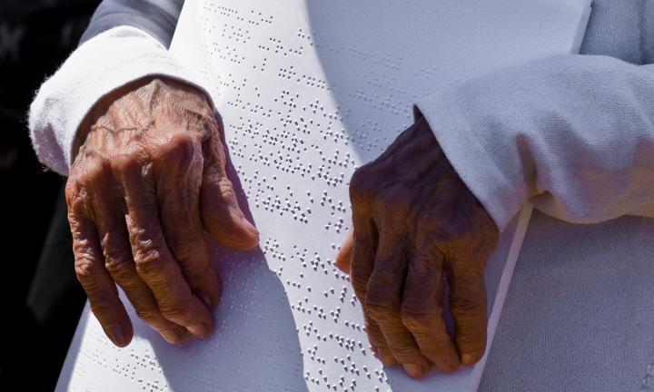 Pessoa a ler folhas Braille
