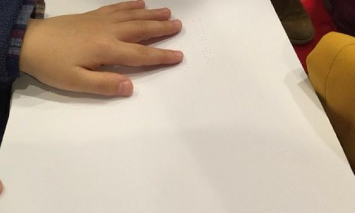 Mão de criança a ler livro Braille