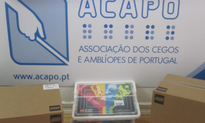 Em frente ao logotipo da ACAPO, uma caixa do Lego Braille Bricks ladeada por caixas de cartão com o logotipo da LEGO.