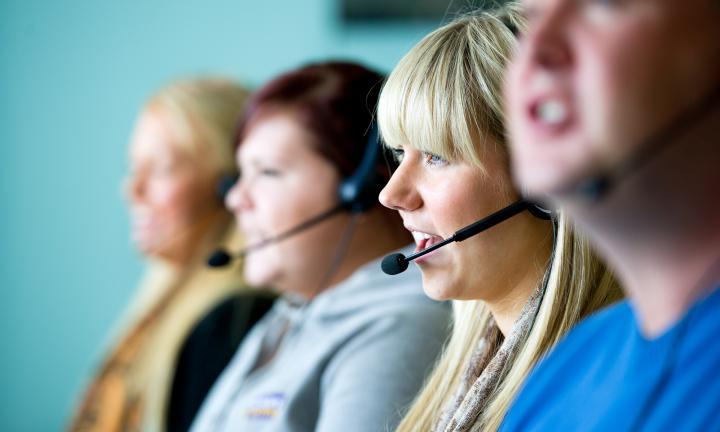 Quatro pessoas de headset a trabalhar em ambiente de contact center