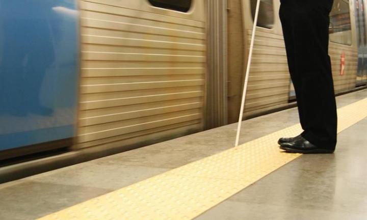 Pessoa com bengala junto a metro